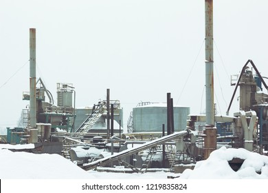Metal construction of an asphalt plant in winter covered with snow