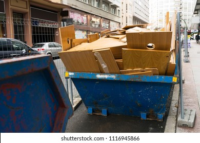 metal container with debris and wood waste in city street