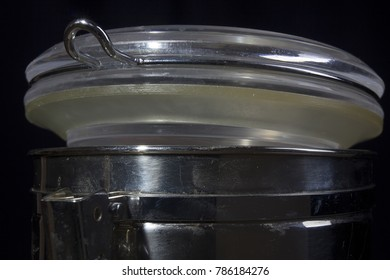 Metal container with a tight lid on a black background
