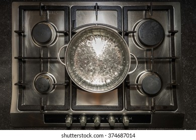 Metal cooking pan with boiling water on a stove