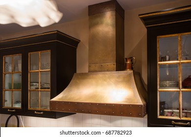 Metal copper kitchen range hood in the classic kitchen interior