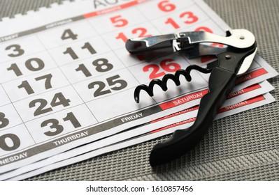 Metal corkscrew and calendar on a textured surface. Weekend concept
