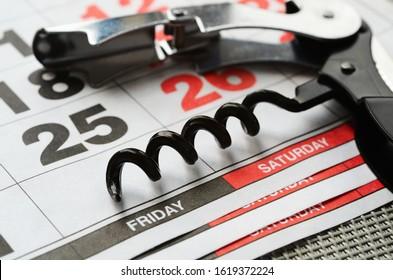 Metal corkscrew and calendar. Weekend concept