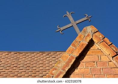 Metal cross on a redbrick building against a blue sky