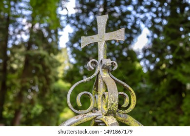 A metal cross with ornaments on a railing in the park