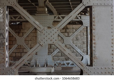 Metal cross-shaped bridge support in rivets, painted gray