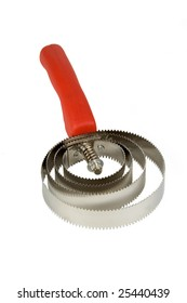 A metal curry comb, with a red handle.