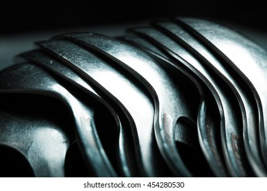 Lot of metal cutlery on a black background. Selective focus. Shallow depth of field. Toned.