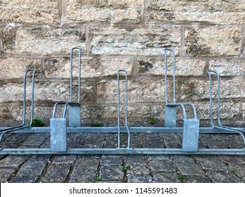 Metal cycle rack on cobble stone ground against rough stone brick wall in sand colors.