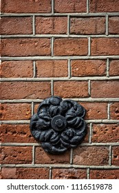 Metal decorative element in the shape of a flower on a brick wall close-up.