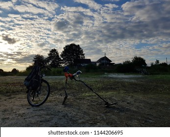 Metal detector, bicycle and shovel in sunrise