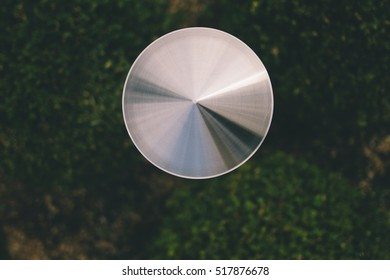 a metal disc on a green background of grass or leaves. Blurred background