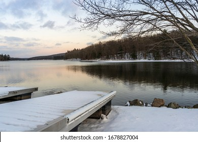 A metal dock sits on a snowy shore while an icy blue sky is reflected in the mirror-like surface of a partially frozen lake in western Maryland, United States.