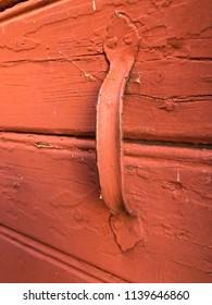 Metal door handle on wooden door, painted in traditional Swedish red color.