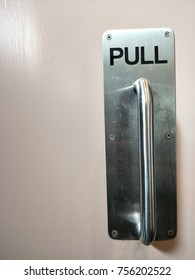 "Metal door handle and word is ""Pull"""