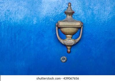 Metal door knocker on blue door