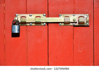 Metal Door Latch with Padlock at an old red painted wood carved House Door