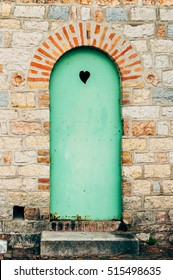 Metal door, painted in green, with a black heart.
