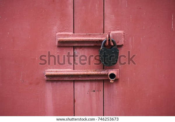 The metal door is red with a padlock. Close-up.