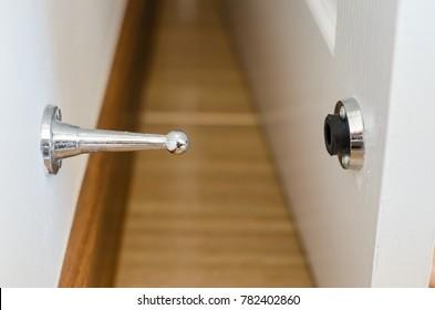 Metal Door Stopper On The Wall And White Door