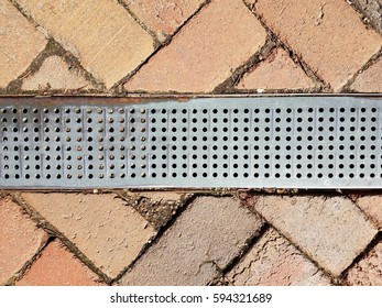 metal drain in brick path