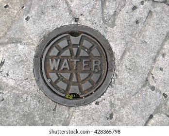 A metal drain cover or water supply on a cement pathway