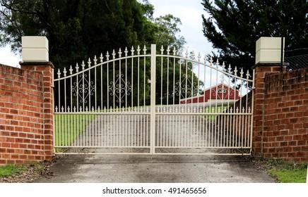 Metal driveway entrance gates set in brick fence