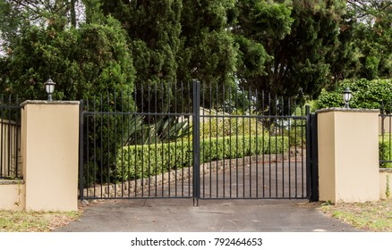 Metal driveway entrance gates set in brick fence with garden trees in background