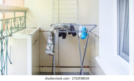 Metal drying rack stands on the balcony, wet clothes are drying and hanging on the dryer on a summer day