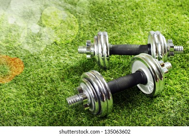 Metal dumbbells on green grass in summer sunshine with bokeh conceptual of fitness, exercise abd a healthy outdoor sporty lifestyle
