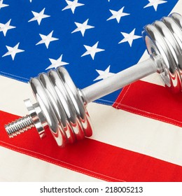 Metal dumbbells over USA flag as symbol of healthy nation - studio shot - 1 to 1 ratio