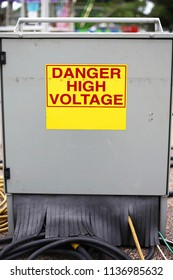 A metal electric power supply junction cabinet box at a carnival has a yellow and red danger high voltage sign on it.