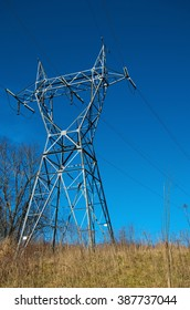 A metal electric utility tower stands at the top of a hill against a brilliant blue sky background.