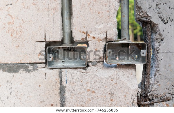the metal electronic and power outlet boxes were installed in the concrete and brick walls of the building