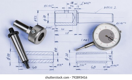 Metal engineering components, gauge and technical drawing. Steel machining jigs and dial gauge micrometer laid on the manufacturing documentation.
