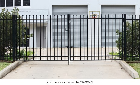 Metal entrance gate with spikes across a driveway