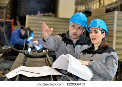 Metal factory manager pointing at something while talking to female apprentice