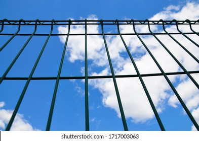 Metal fence close-up. Fence against a background of blue sky and white clouds. Look up.