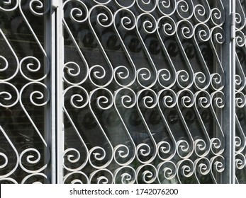 a metal fence formed by gray painted spirals in a grid