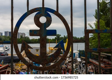 A metal fence with an image of an anchor. Silhouette of an anchor in the fence and sea port. Metal anchor in cirkle in metal gate