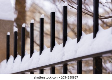 Metal fence outside under a heavy snow