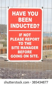 A metal fence with a red and white sign asking workers 'HAVE YOU BEEN INDUCTED' with further information underneath.