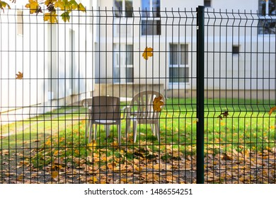 metal fence for street fencing, autumn leaves, nursing home, two plastic chairs