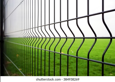 Metal fence wire, grass and sky in the background