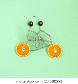 Metal figures of sportsmen with cherry head on bicycle with wheels from orange on green pastel background. Minimal style. Concept of healthy lifestyle, dietary and sports food