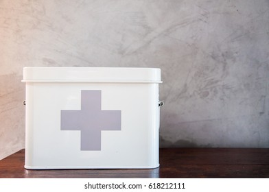 Metal first aid kit box on wooden table