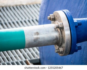 metal flange with bolts, for the coupling of a tube with a blue fiberglass tank, in an industrial environment