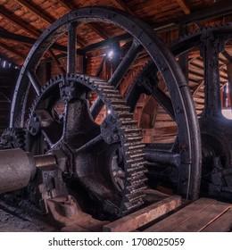 Metal flywheel inside the wooden old factory