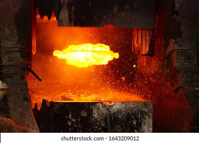 metal forging. hydraulic hammer shapes the red hot billet. the production of high tech parts.