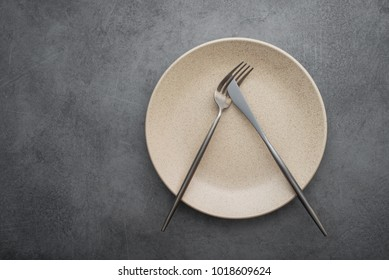 Metal fork and knife on a stone table. arrangement of cutlery after meals. top view